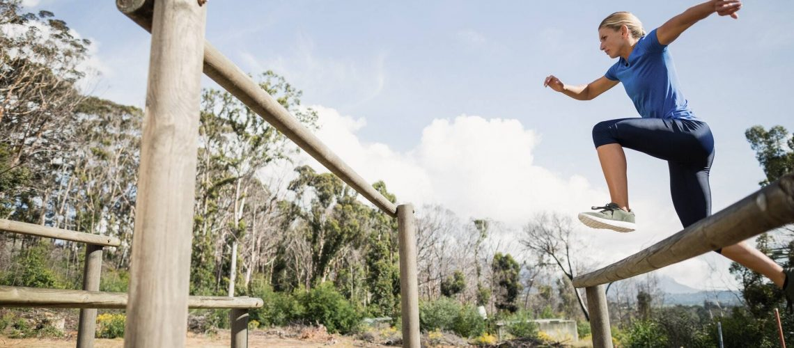 Woman jumping over the hurdles during obstacle course
